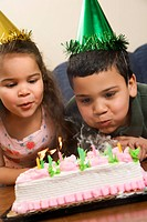 Hispanic girl and boy wearing party hats blowing out candles on birthday cake