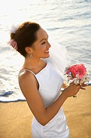 Young adult female Caucasian bride holding bouquet on beach