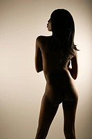 Nude African American mid adult woman with back to viewer looking to side