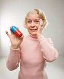 Caucasian senior woman holding oversized pill at viewer.
