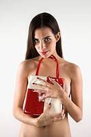 Topless Caucasian woman holding purse to her chest