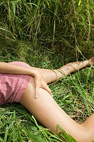 Young Caucasian woman lying in grass with skirt hiked up and hand on thigh