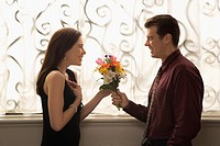 Mid adult Caucasian man presenting surprised woman with bouquet of flowers (thumbnail)