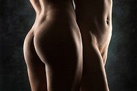 Hips and buttocks of nude Hispanic and Caucasian women standing together