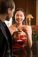 Taiwanese mid adult woman and Caucasian man toasting martinis