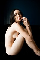 Nude young adult Caucasian woman sitting with fingers to mouth