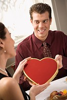 Mid adult Caucasian man giving a heart shaped box of chocolates to surprised woman at restaurant