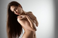 Topless Caucasian woman with arms crossed looking to the side