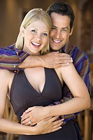Caucasian mid adult couple embracing and smiling at viewer