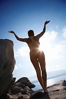 Silhouette rear view of nude Caucasian woman standing saluting the sun overlooking Pacific Ocean