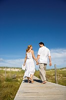 Caucasian mid_adult couple holding hands walking down beach access path
