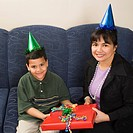 Mother and son wearing party hats holding birthday presents smiling and looking at viewer