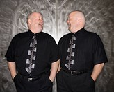 Caucasian bald mid adult identical twin men looking at each other laughing