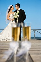 Pair of flute glasses of champagne with Caucasian bride and groom in background