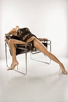 Attractive woman in lingerie leaning back seductively on chair.