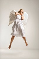 Caucasian mid_adult woman in white angel costume jumping in air