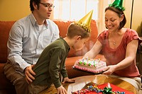 Caucasian boy in party hat blowing out candles on birthday cake with family watching