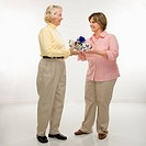 Caucasian senior woman and middle aged woman exchanging a gift