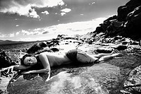 Nude Caucasian mid adult woman lying in tidal pool at coast with eyes closed and head on arm