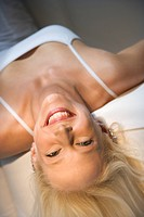 Portrait of attractive blonde Caucasian young adult woman lying upside down smiling and looking at viewer