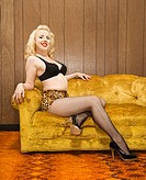 Attractive Caucasian woman in lingerie posing on retro couch