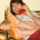 Caucasian mid_adult man talking on telephone with Caucasion mid_adult woman's legs draped over lap