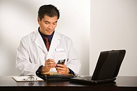 Asian American male doctor sitting at desk with charts and laptop computer using pda