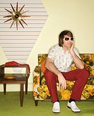 Caucasian mid-adult man wearing sunglasses sitting on colorful retro sofa looking bored (thumbnail)