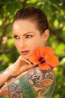 Attractive Caucasian tattooed woman with Hibiscus flower over her shoulder
