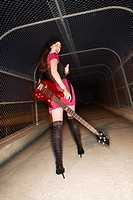 Caucasian young adult female walking with electric guitar in skywalk looking at viewer and gesturing