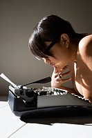 Nude young Asian woman sitting at kitchen table reading paper in typewriter