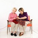 Caucasian middle aged woman and senior woman sitting and knitting