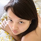 Head and shoulder portrait of pretty young Asian woman lying in bed making eye contact