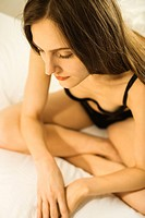 Caucasian mid_adult woman sitting on bed in lingerie with legs crossed