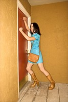 Caucasian young adult woman in retro clothing pounding fists on door and yelling