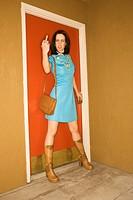 Caucasian young adult woman in retro clothing standing beside door making obscene gesture