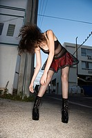 Pretty Caucasian young woman standing flinging hair in urban setting