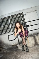 Portrait of pretty Caucasian young woman giving middle finger in urban setting