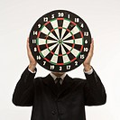 Caucasian man wearing suit and holding dartboard in front of face
