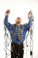 African American businessman wrapped in computer cables