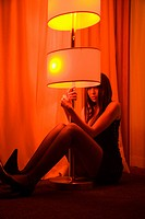 Pretty Caucasian young woman sitting on floor holding floor lamp