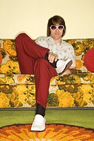 Caucasian mid_adult man sitting on colorful retro sofa wearing sunglasses looking bored