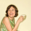 Pretty Caucasian mid_adult woman holding up coffee cup and smiling