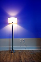 Blue projection light on wall with bright floor lamp