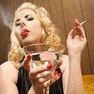 Woman holding a martini and smoking a cigarette