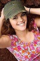 Young Caucasian woman wearing hat with hands behind head smiling at viewer