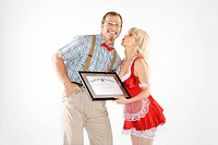 Caucasian young man dressed like nerd receiving kiss and certificate from Caucasian young blonde woman dressed in french maid outfit