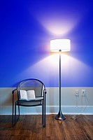 Blue projection light on wall with bright floor lamp and open book on chair