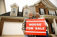 Portrait of middle_aged African_American couple outside house with for sale sign