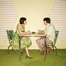 Caucasian mid_adult man and woman wearing vintage clothing sitting at 50's retro dinette set facing each other